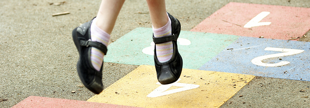 Feet of a girl doing hopscotch